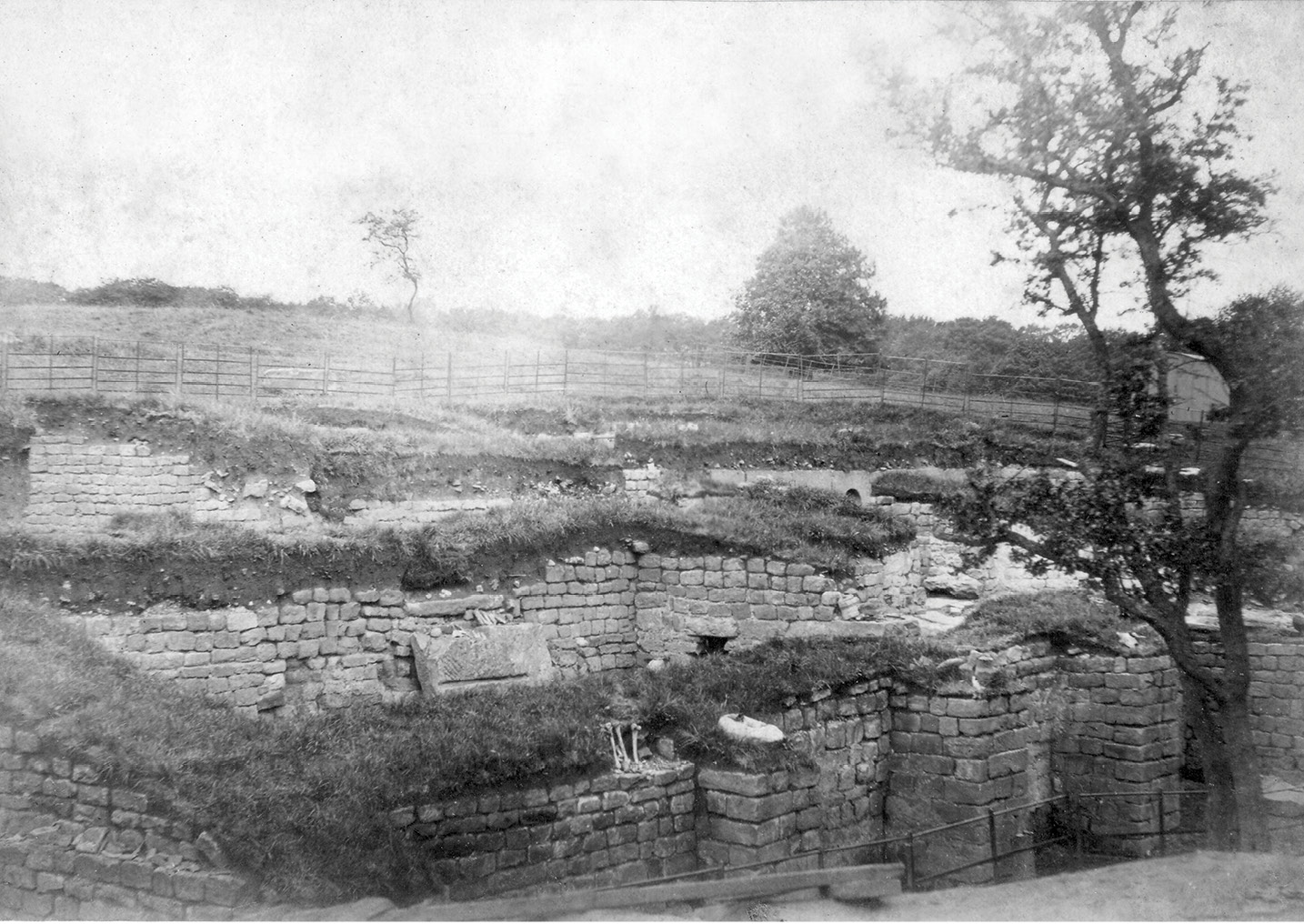 below A photograph of the bathhouse at Chesters fort, taken during excavations in 1885. In the foreground is the outer wall of a hot room, with human bones lying on it. Did these come from a cemetery beyond the bathhouse walls?