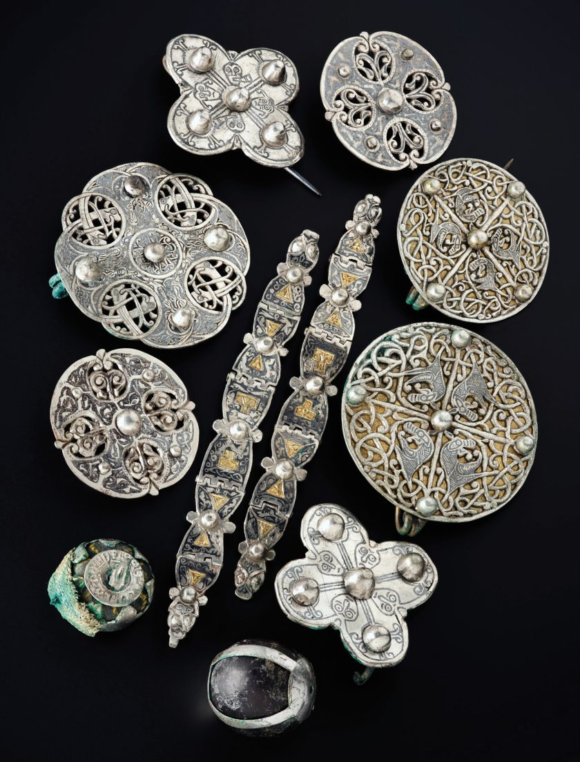 below Anglo-Saxon metalwork recovered from inside a lidded vessel in the Galloway Hoard, including seven brooches, a pair of multi-hinged straps, a 'relic' pendant made from a bead enclosed in silver and a perforated coin (bottom left), and a rock crystal sphere in a broken silver pendant-fitting (bottom centre).