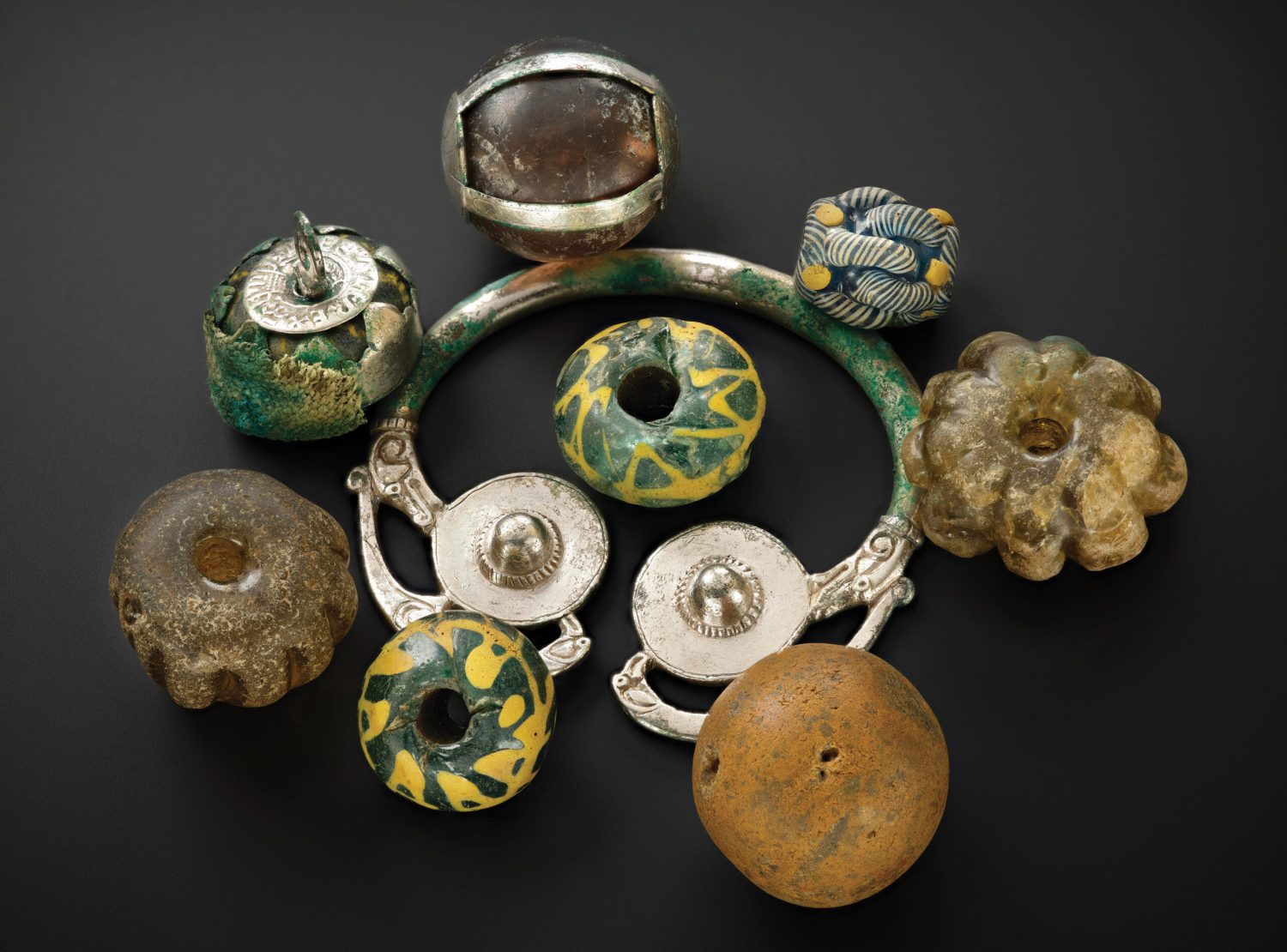 above Beads, curios, and heirloom objects were found together as a group resting on a silver brooch-hoop at the top of the lidded vessel in the Galloway Hoard.
