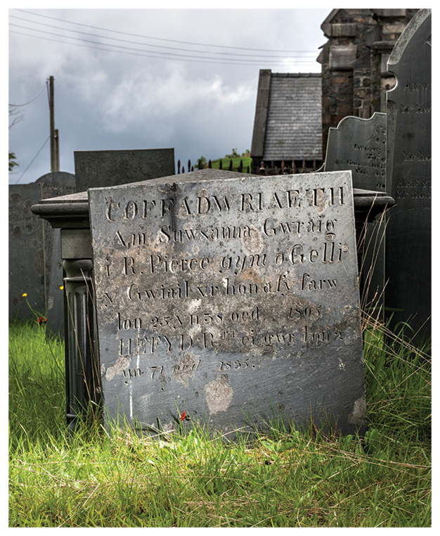 below Slate is commonly used in rural Wales for gravestones such as this monument to Suwsanna Pierce (d. 1805) in St Michael's churchyard in the slate village of Ffestiniog; this is also the earliest slate block identified so far with the circular striations that indicate the use of a mechanised circular saw. bottom Slate fences are found across the county of