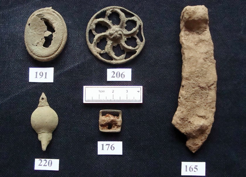 above The pendant (top left), horseshoe fragments (top centre and right), sword-belt support (bottom left) and buckle (bottom centre) found during the survey.