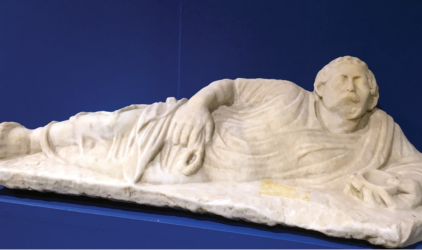 below A marble statue of a moustachioed man reclining on a dining couch at Genoa's Museo di Archeologia Ligure.