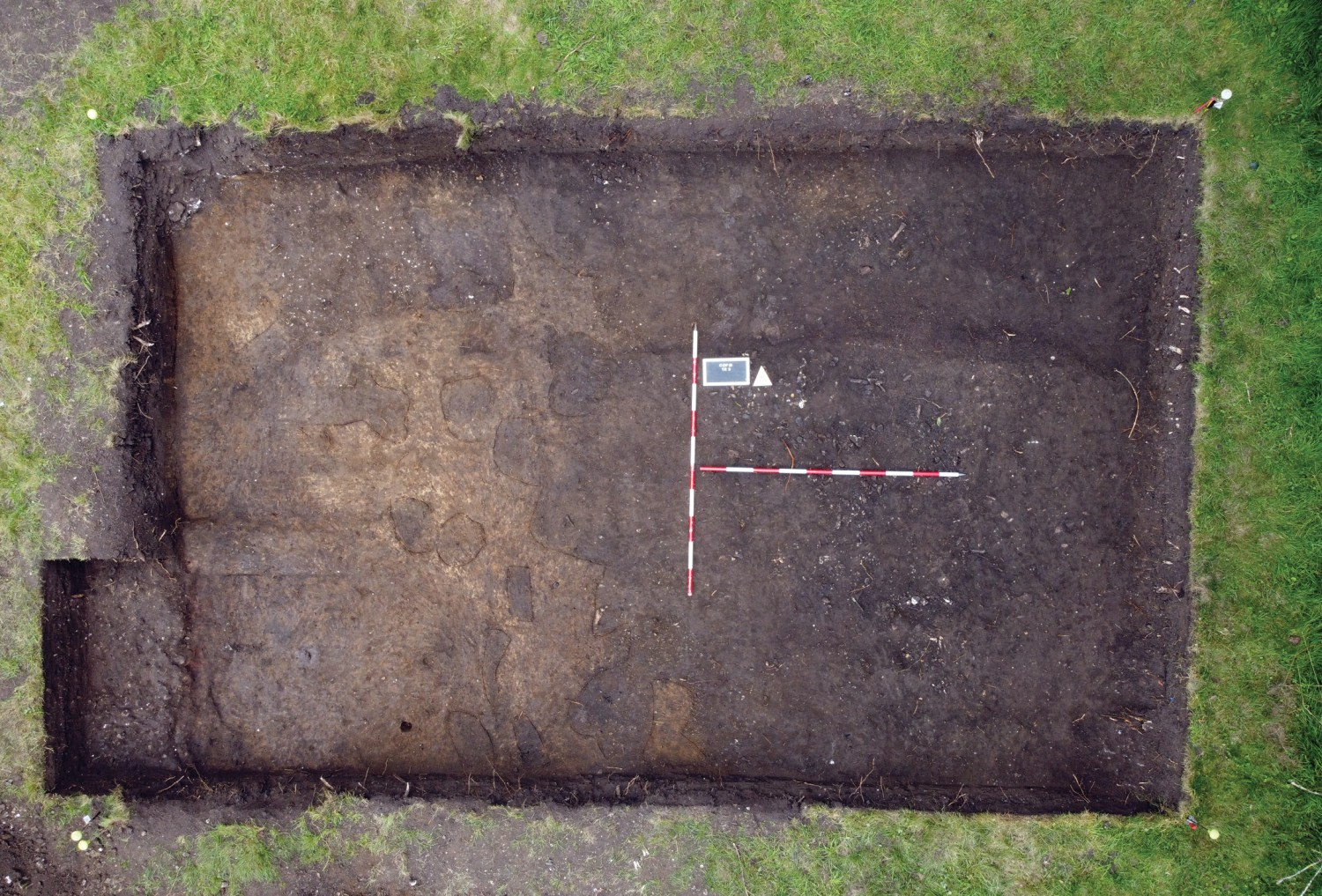 above An extensive midden spread, represented by dark material strewn with fragments of animal bone, covers more than half of this trench. Post-holes cut into the yellow natural geology can be seen to its left.