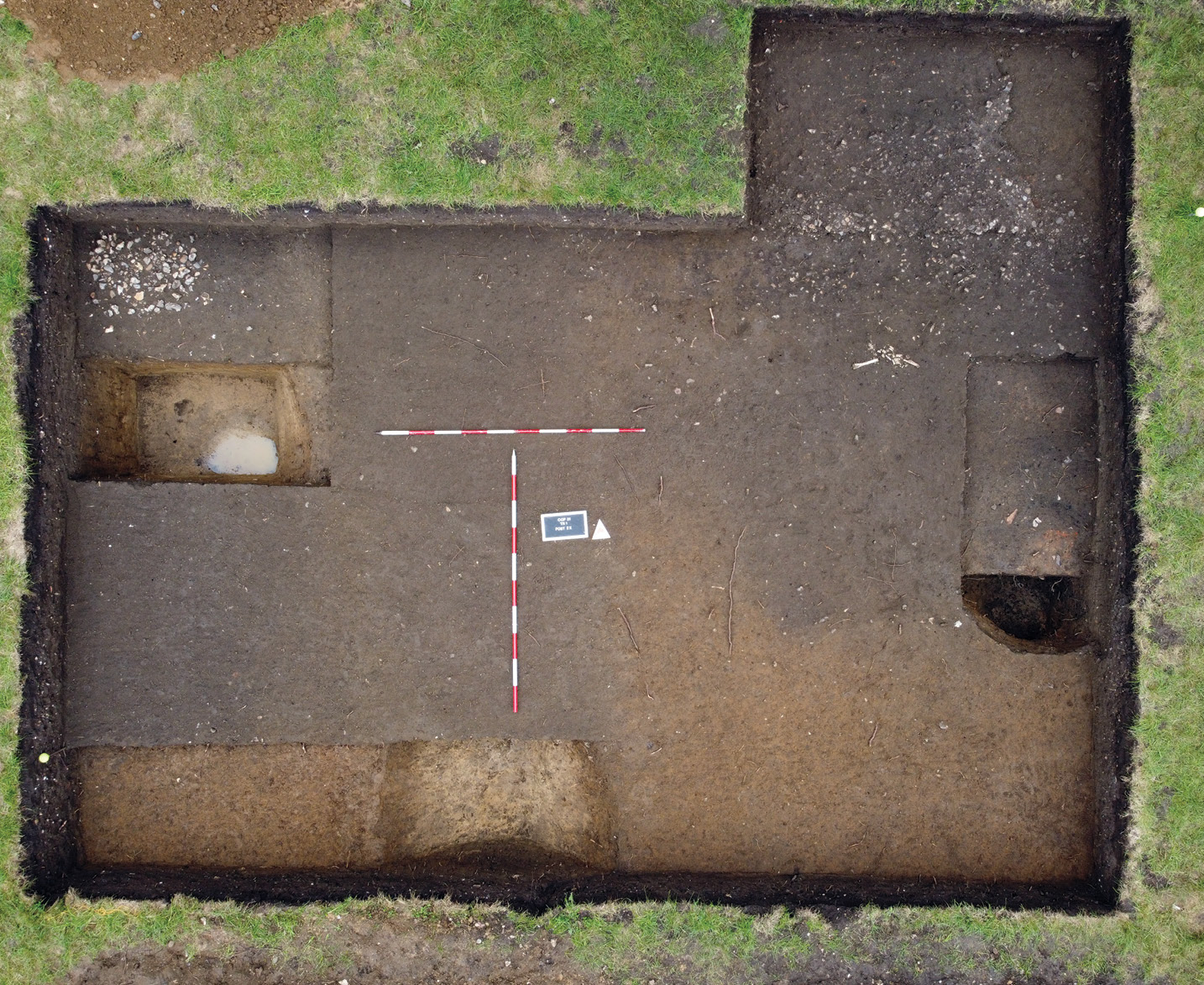 below This trench preserves a portion of a metalled surface/trackway in its top right area. Such routeways represent significant investment in infrastructure on the site. Partially excavated pits (shown extreme left and right) and a section of ditch (bottom) can also be seen.