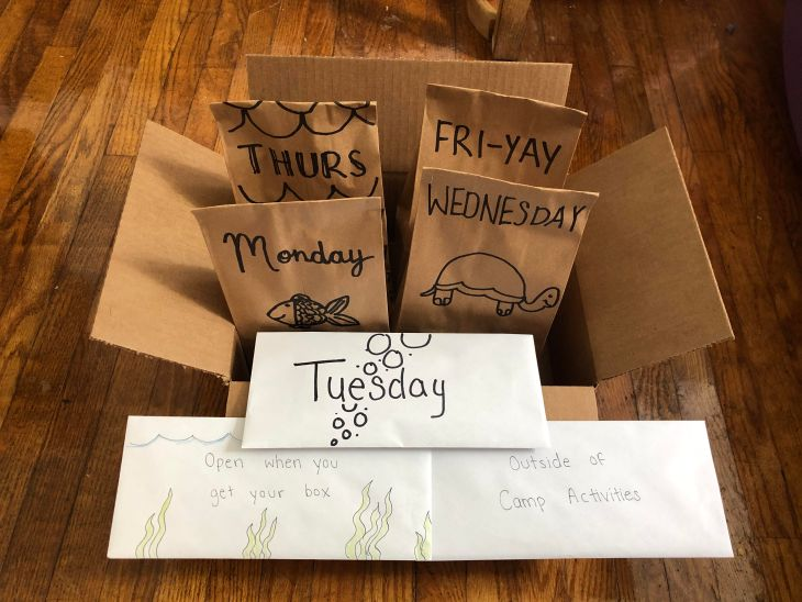 """Four paper bags labelled """"Monday, Wednesday, Thurs, Fri-Yay"""" sit in a cardboard box."""