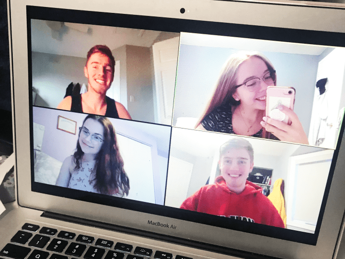 A photo of a Zoom screen, with four young people smiling.