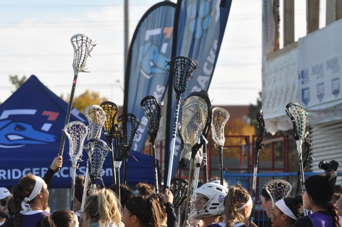 The women's lacrosse team at Western University hold their lacrosse sticks in the air