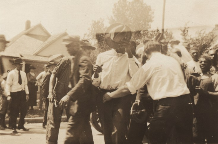 Group of Black men pushed together and led past white onlookers