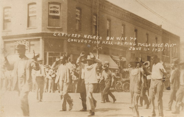 Black men being marched with their hands raised over heads down city street