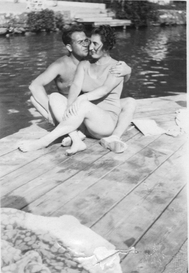 A photograph of a couple sitting together on a dock.