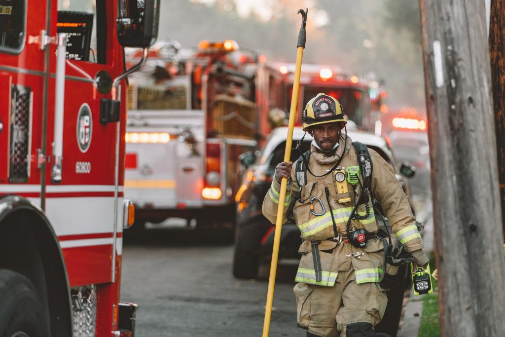 A firefighter walking towards a fire. 90% of firefighters today must be EMT certified.