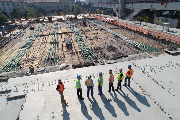 Construction workers in hard hats and safety vests survey the scene on a job site. If you study construction technology at  San José City College you can launch your career in construction.