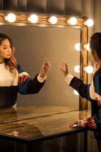 Young lady looking at herself in the mirror and pointing while she says her affirmations