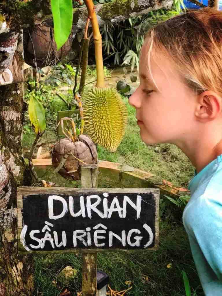 phu quoc with kids - girls smelling durian fruit on pepper farm in phu qouc