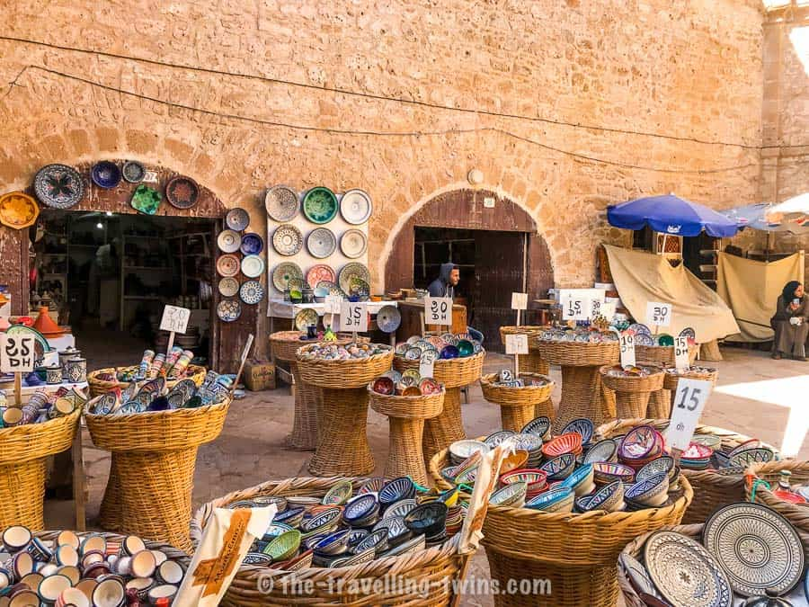 various design ceramic plates, tajine display in baskets on market in Essaouira