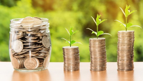 Piles of coins with green shoots sprouting out the top, demonstrating the importance of impact investing and using your money to make positive change.