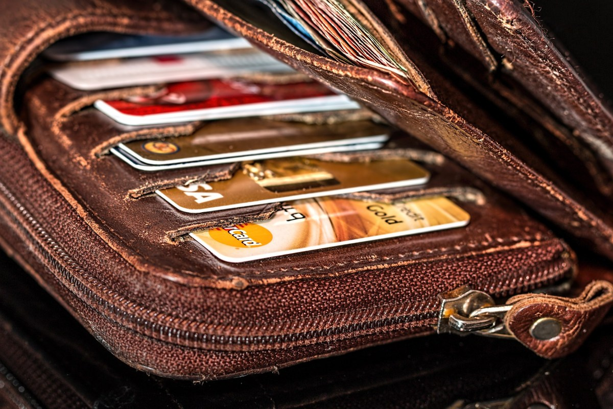 Take control of your debt. A large wallet, filled with lots of credit cards.