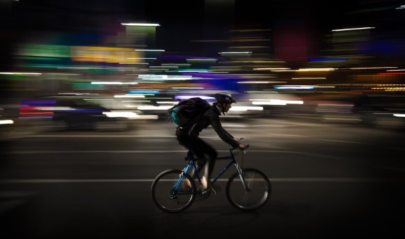 Deliveroo IPO - cyclist carrying a large bag through a busy city at night.