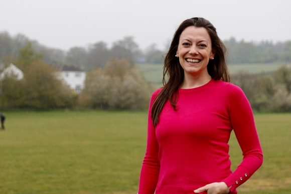 Sarah Green - woman wearing a red jumper smiling in a big field