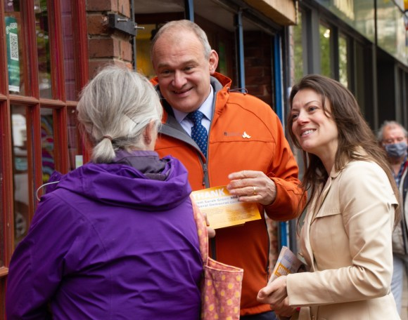 A man and a women holding leaflets, speaking to an older woman in a purple jacket