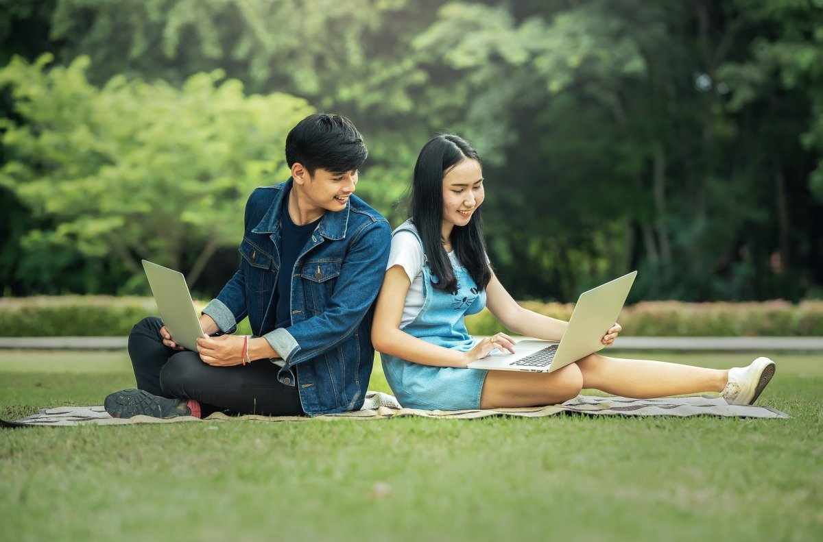 Young couple sat back to back with laptops