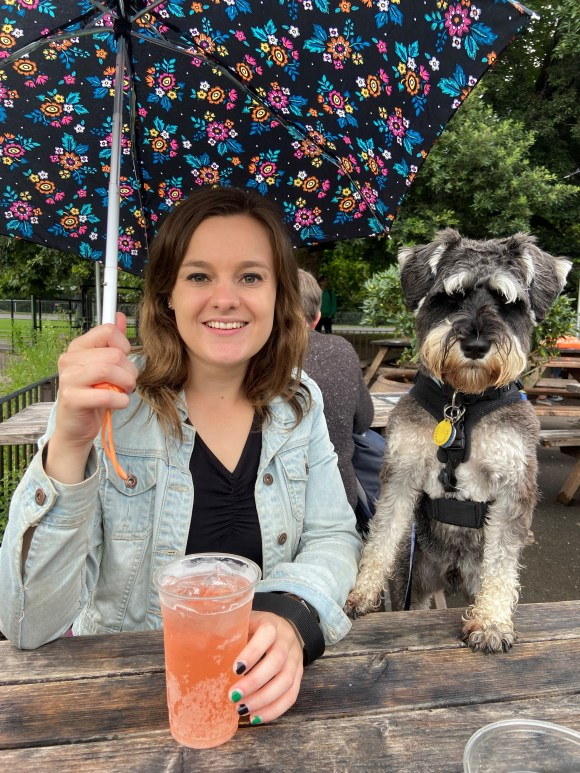 girl holding flowery umbrella and miniature schnauzer smiling at the camera.