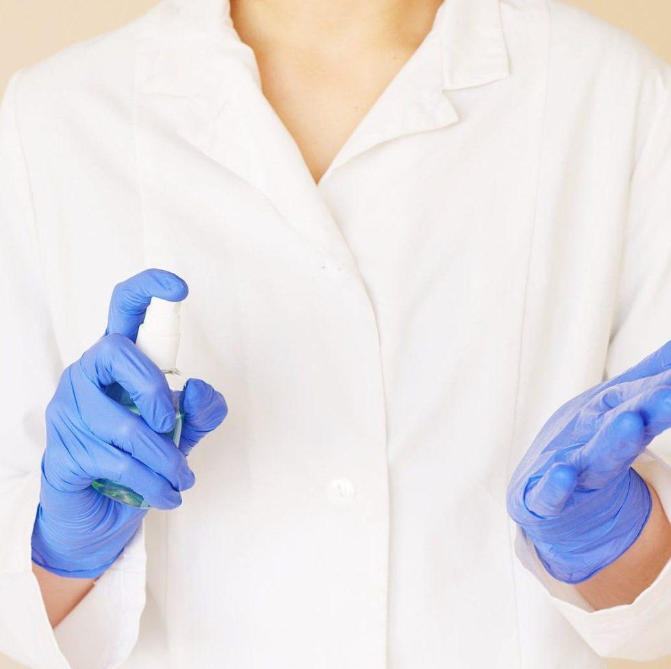crop medical worker spraying sanitizer over hands in gloves