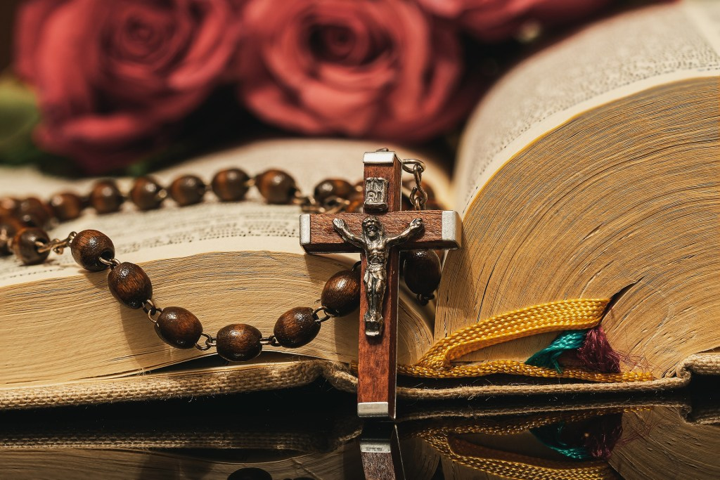 Photo of rosary beads draped over a bible by Myriam Zilles