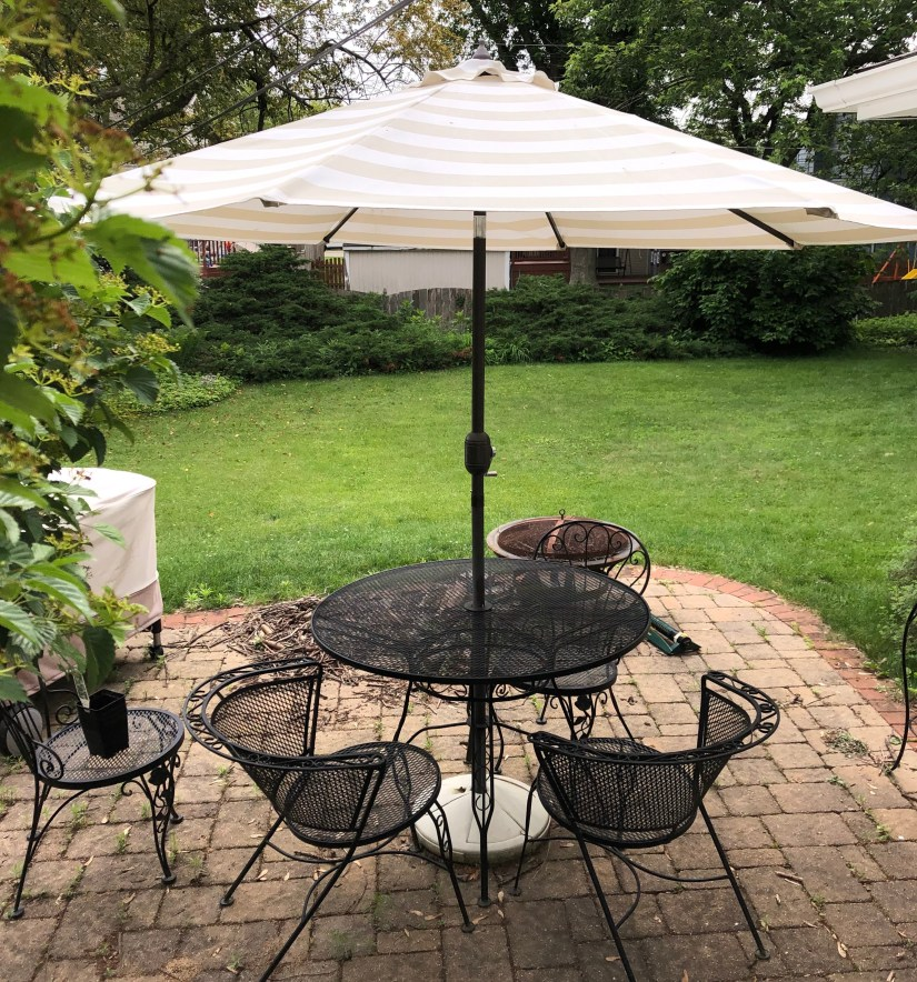 black wrought-iron patio table and chairs with beige and white striped umbrella