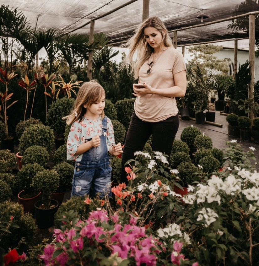 mom and daughter looking at flowers in the garden center