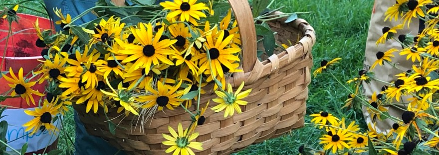 brown hand woven basket filled with yellow flowers