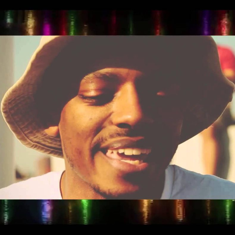 a closeup of Lucid00 wearing a bucket hat, open mouth smiling with his eyes closed.