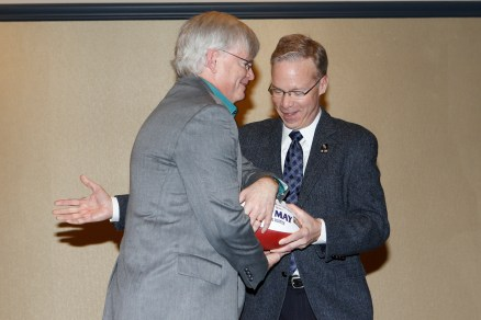Beat Write of the Year Tim May of the Columbus Dispatch receives a commemorative football from Malcolm Moran. Photo by Melissa Macatee.