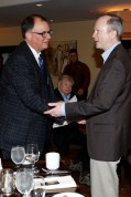 2015 FWAA President Lee Barfknecht greets member Steve Wieberg, who serves on the CFP Selection Committee, at the FWAA's annual Awards Breakfast on Jan. 11 in Scottsdale, Ariz. Photo by Melissa Macatee.