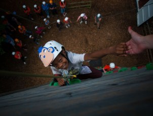 A camper may zip to the top of the climbing wall. Their challenge might be to do it blindfolded.