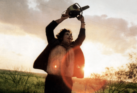 The iconic image of Leatherface wildly swinging his chainsaw in the middle of the raod