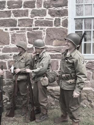 Soldiers relaxing beside a building, conversing and enjoying a bit of downtime. Credit: Grace Nastis.