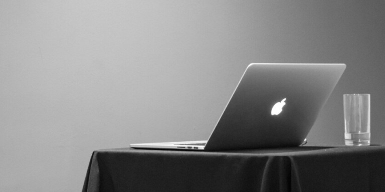 Apple laptop and glass of water on a table