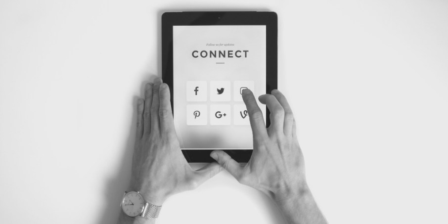 Hands hold tablet with social media icons and the word 'connect'