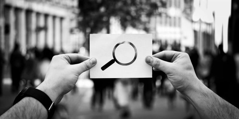 Hands holding up white notecard with search icon (magnifying glass) on it