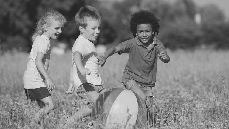 Three children play in a field chasing after a ball