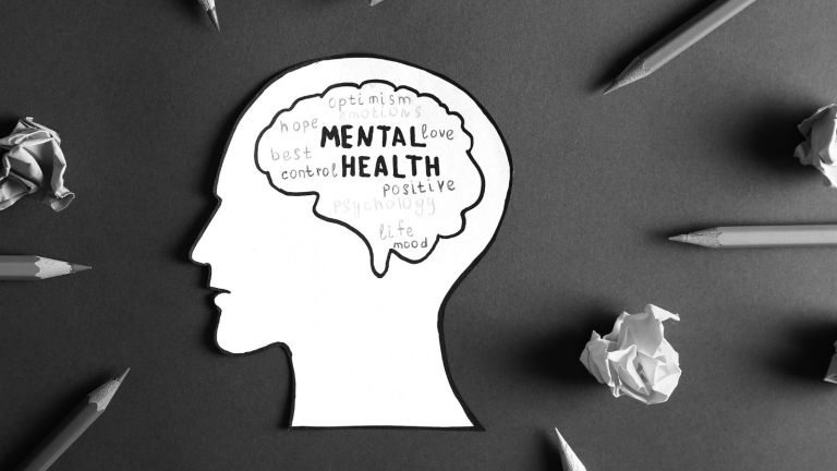 """Paper cutout of a head with the brain outlined in pen, inside reads """"mental health"""" and positive words, cutout surrounded by pencils and crumpled paper"""