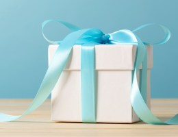 A wrapped gift box tied with a long blue ribbon