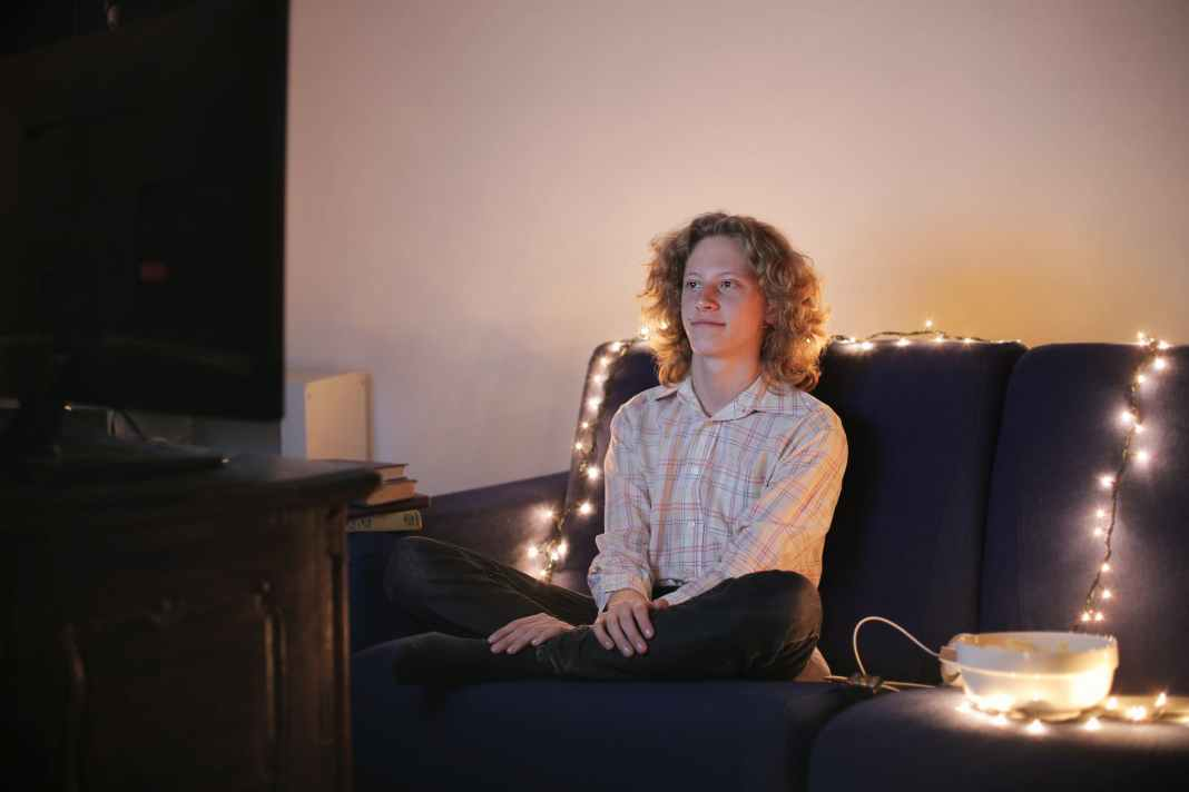 relaxed young man watching tv in living room in evening
