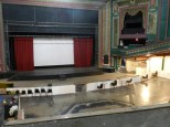 The stage was likely meant for movie theater viewings and vaudeville acts when built in 1919, reminiscent of the grand theaters of the 20s, but has since been used as a Christian space, a bar, a meeting space, and a music venue.