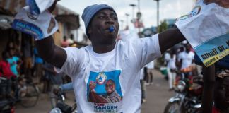 A supporter of the National Grand Coalition waves campaign posters during a rally in Bo, Sierra Leone, on March 4, 2018. (J. Patinkin/VOA)