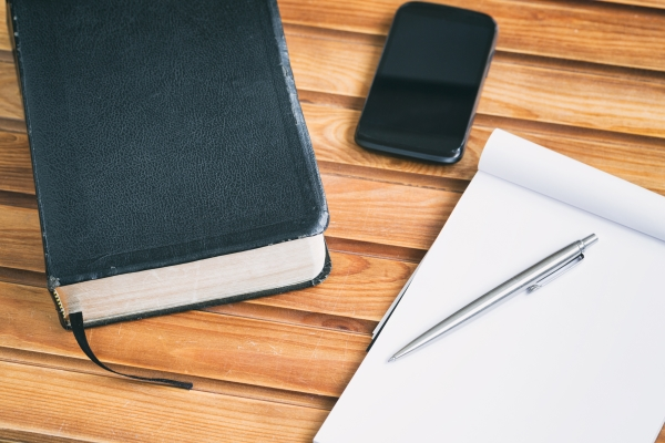 ministries Bible study materials - a Bible, notebook and a smartphone over a wooden surface.