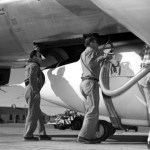 "Technicians servicing the Bell Aircraft Corporation X-1 in preparation for a flight. The X-1 is mated with the Boeing B-29. The hooks and strap that holds the X-1 in place under the B-29 can be seen just above the hand of the technician with the hose. The strap continues under the belly of the X-1 and holds the aircraft to the mothership until the word comes to ""launch"", and then the shackles are released. (NASA photo)"