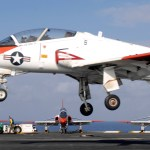 A T-45 Goshawk assigned to Training Airwing One flies by three other chocked-and-chained Goshawks while approaching for an Touch and Go on board r USS Harry S. Truman in 2007 (US Navy photo)