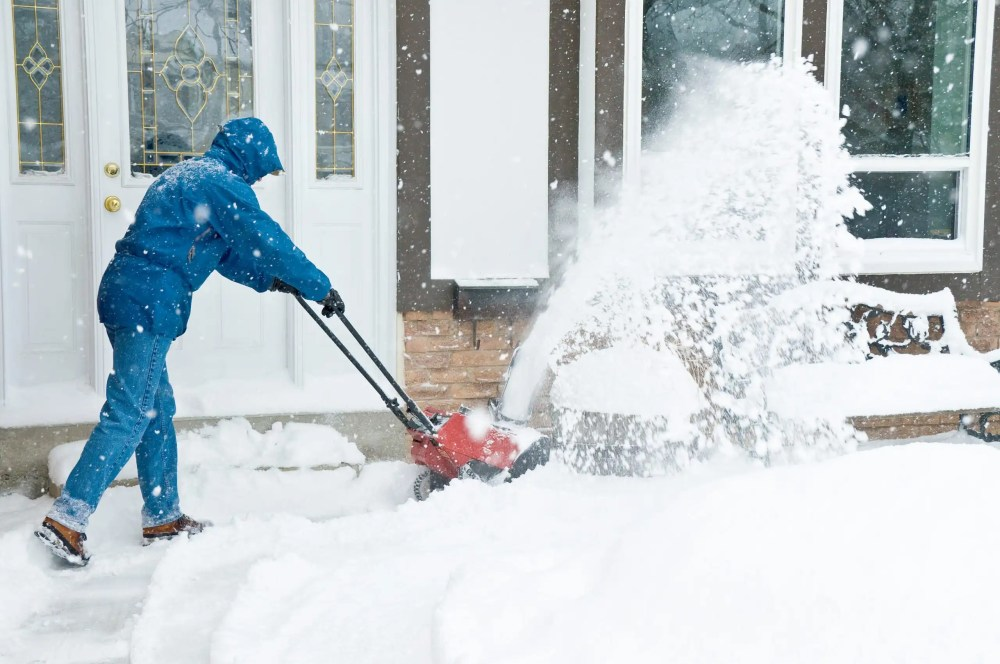 battery powered snow blower removing snow